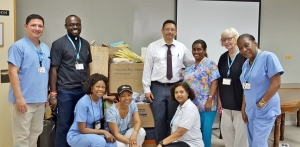 The Missionaries with Hospital CEO at Karl Huesner Memorial Hospital, Belize City. From L-R (Standing):  Christopher Rodriquez, Father Tony Holder, CEO of the K.H.M. Hospital, Dr. Adrian Coye,  Dr. Patricia Rowe-King, Linda Schlepp-Gray, and Dr. Arlene Richards. From L-R (Squatting):  Carlene Nugent, Erna Cunningham, Bibi Achaibar.